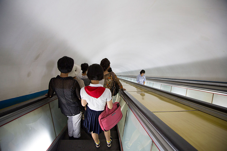 "Descending into the Pyongyang Metro, reportedly one of the deepest metros in the world. Rumors persist that the Pyongyang Metro doubles as giant bomb shelter, linking vast underground military installations to one another, with secret lines just for the government, and escape tunnels to China. Rumors also persist that ""normal"" people actually use it."